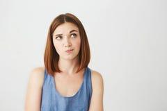 Muchacha hermosa joven que mira para arriba de pensamiento aumentando la frente sobre el fondo blanco Imágenes de archivo libres de regalías