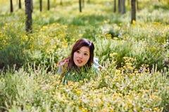 Muchacha hermosa joven que pone en el campo de flores Imágenes de archivo libres de regalías