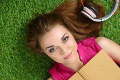 Muchacha hermosa joven que pone en la hierba en el parque que sostiene un libro Foto de archivo libre de regalías
