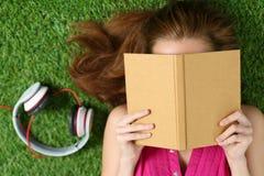 Muchacha hermosa joven que pone en la hierba en el parque que sostiene un libro Fotografía de archivo libre de regalías