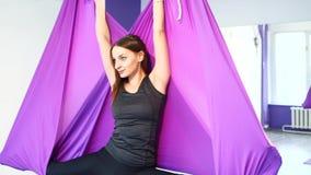 Muchacha hermosa joven que practica yoga aérea en gimnasio metrajes