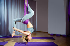 Muchacha hermosa joven que practica yoga aérea en gimnasio Fotos de archivo libres de regalías