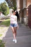 Muchacha hermosa joven que presenta una ciudad de la moda en pantalones cortos cortos del dril de algodón, blusa y mujer atractiv Imágenes de archivo libres de regalías