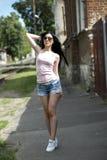 Muchacha hermosa joven que presenta una ciudad de la moda en pantalones cortos cortos del dril de algodón, blusa y mujer atractiv Fotos de archivo