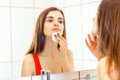 Muchacha hermosa joven que se coloca al lado de un espejo y de trapos la cara con un disco del algodón Fotografía de archivo
