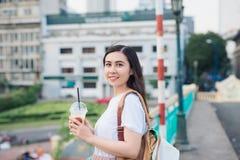 Muchacha hermosa joven que se coloca en un puente con la opinión de la ciudad con el co Imágenes de archivo libres de regalías
