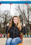 Muchacha hermosa joven que se divierte que monta un cadena-oscilación en el parque Foto de archivo