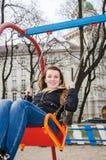 Muchacha hermosa joven que se divierte que monta un cadena-oscilación en el parque Imagen de archivo libre de regalías