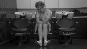 Muchacha hermosa joven que se sienta en butaca con el lavabo en salón profesional Fotografía de archivo libre de regalías