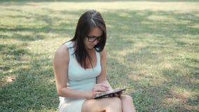 Muchacha hermosa joven que se sienta en césped en el parque usando Tablet PC, concepto en línea de las compras metrajes