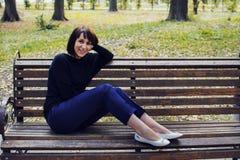 Muchacha hermosa joven que se sienta en un banco Foto de archivo