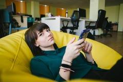 Muchacha hermosa joven que se sienta en un bolso de la butaca, sosteniendo un teléfono y mirando la cámara Relájese en la rotura Imágenes de archivo libres de regalías