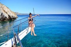 Muchacha hermosa joven que se sienta en un yate en el mar Relajación en el agua Fotografía de archivo