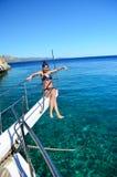Muchacha hermosa joven que se sienta en un yate en el mar Relajación en el agua Fotos de archivo