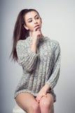 Muchacha hermosa joven que se sienta en una silla En un fondo blanco En un suéter gris Photosession de una morenita atractiva Foto de archivo