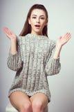 Muchacha hermosa joven que se sienta en una silla En un fondo blanco En un suéter gris Photosession de una morenita atractiva Fotografía de archivo