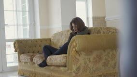 Muchacha hermosa joven que se sienta y que se relaja con la tableta en el sofá en sala de estar acogedora y la sonrisa alegre a l metrajes