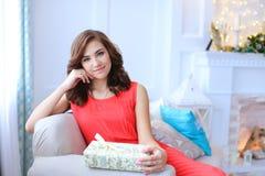 Muchacha hermosa joven que sonríe, sentándose en el sofá y sosteniendo el regalo Foto de archivo