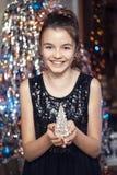 Muchacha hermosa joven que sonríe y que sostiene un árbol de navidad En el vestido negro feliz Fotografía de archivo libre de regalías
