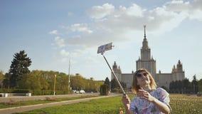 Muchacha hermosa joven que toma la imagen del palillo del selfie feliz el día soleado almacen de video