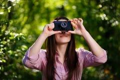 Muchacha hermosa joven que toma las fotos con la cámara retra de la película en Imagen de archivo