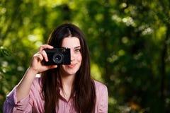 Muchacha hermosa joven que toma las fotos con la cámara retra de la película en Foto de archivo
