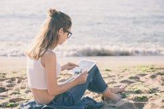 Muchacha hermosa joven que usa una tableta digital por el mar Imagen de archivo libre de regalías
