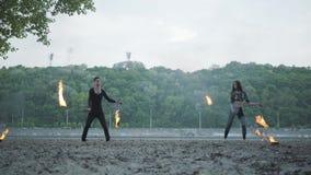 Muchacha hermosa joven y hombre hermoso en la ropa negra que realiza la demostración con la llama que se coloca en el riverbank L almacen de metraje de vídeo