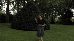 muchacha hermosa 4k en el vestido hecho a mano negro que hace selfy con su smartphone móvil en el jardín de hadas del bosque de l almacen de video