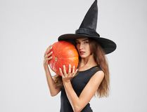 Muchacha hermosa, mágica de la bruja en un sombrero, sosteniendo una calabaza en un fondo gris Concepto de Víspera de Todos los S Imágenes de archivo libres de regalías