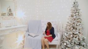 Muchacha hermosa misma que sostiene un regalo del Año Nuevo en sus manos almacen de video