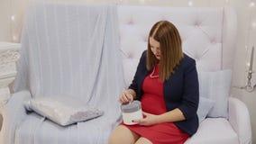 Muchacha hermosa misma que sostiene un regalo del Año Nuevo en sus manos almacen de metraje de vídeo