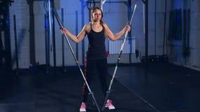 Muchacha hermosa muscular en el negro superior y las polainas negras que hacen un ejercicio con un barbell en el gimnasio en un i almacen de video