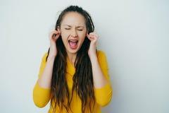 Muchacha hermosa obstinada enojada subrayada con los dreadlocks y en un suéter brillante amarillo que pega los fingeres del enchu fotografía de archivo libre de regalías