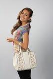 Muchacha hermosa oscura en un estilo de moda con un bolso blanco Imagen de archivo libre de regalías