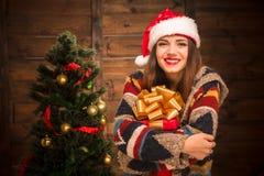 Muchacha hermosa que abraza un actual árbol cercano del Año Nuevo Foto de archivo libre de regalías