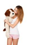 Muchacha hermosa que abraza un perro del peluche Foto de archivo libre de regalías