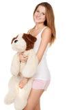 Muchacha hermosa que abraza un perro del peluche Imagen de archivo libre de regalías