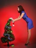 Muchacha hermosa que adorna el árbol de navidad Foto de archivo