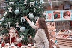 Muchacha hermosa que adorna el árbol de navidad con las bolas de la decoración Fotos de archivo libres de regalías