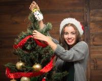 Muchacha hermosa que adorna el árbol del Año Nuevo en casa Imagen de archivo