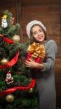 Muchacha hermosa que adorna el árbol del Año Nuevo en casa Imágenes de archivo libres de regalías