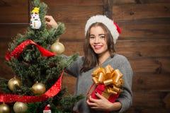 Muchacha hermosa que adorna el árbol del Año Nuevo en casa Fotografía de archivo libre de regalías