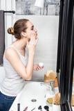 Muchacha hermosa que aplica la crema en su cuarto de baño con los accesorios de la belleza Imagenes de archivo