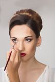 Muchacha hermosa que aplica maquillaje del artista de maquillaje Imagen de archivo