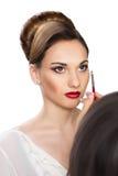 Muchacha hermosa que aplica maquillaje del artista de maquillaje Imágenes de archivo libres de regalías