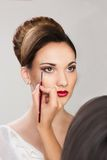 Muchacha hermosa que aplica maquillaje del artista de maquillaje Fotos de archivo libres de regalías
