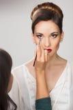 Muchacha hermosa que aplica maquillaje del artista de maquillaje Fotografía de archivo libre de regalías