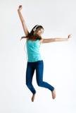 Muchacha hermosa que baila y que escucha la música En blanco Fotografía de archivo