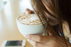 Muchacha hermosa que bebe el café o el té caliente en café del café Foto de archivo